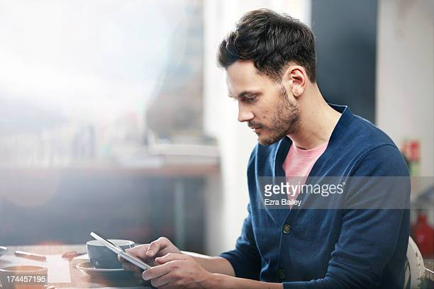 Man working on a tablet in a coffee shop.
