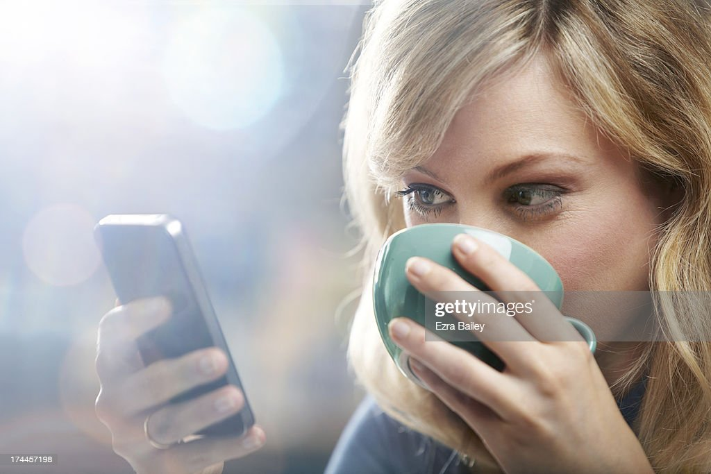 Woman using phone and drinking coffee. : Stock Photo