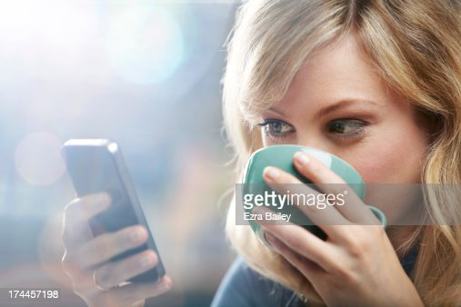 Woman using phone and drinking coffee.