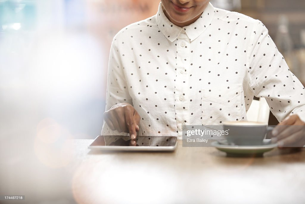 Woman using a tablet in a coffee shop. : Stock Photo