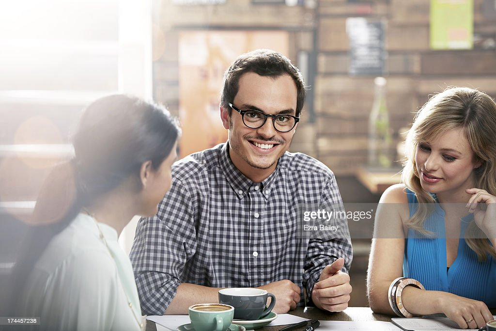 Man smiling in a coffee shop with friends. : Stock Photo
