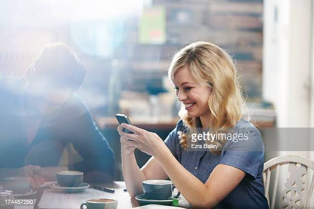 Woman smiling using her phone in a coffee shop.