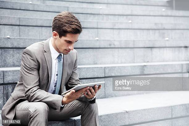 Businessman working outside on a tablet.