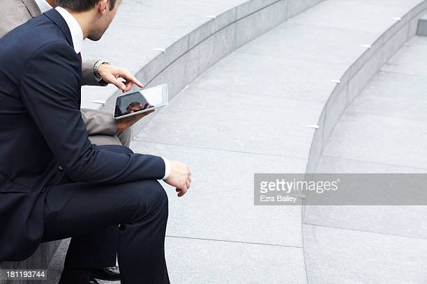 Two businessmen working outside on a tablet.