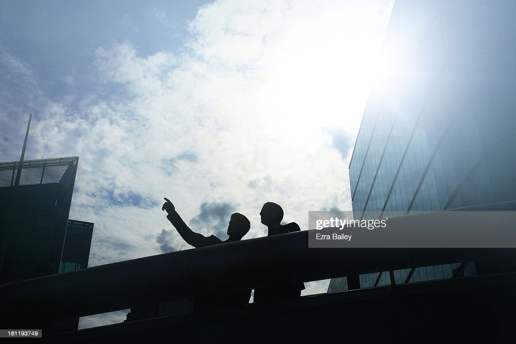 Two businessmen looking out over city skyline, : Stock Photo