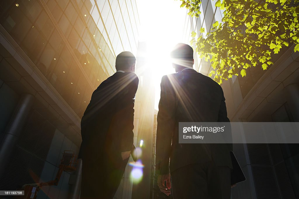 Two businessmen looking up into the sun. : Stock Photo