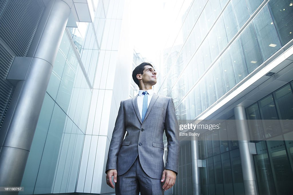 Businessman looking up at city skyline : Stock Photo