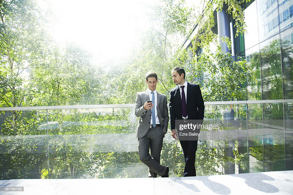 Two businessmen chatting surrounded by trees. : Stock Photo