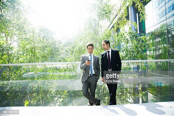 Two businessmen chatting surrounded by trees.