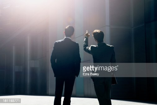 Two businessmen looking up at city skyline.