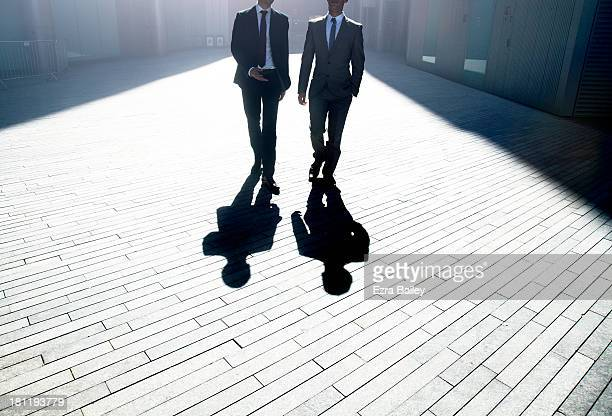 Two businessmen walking through the city.