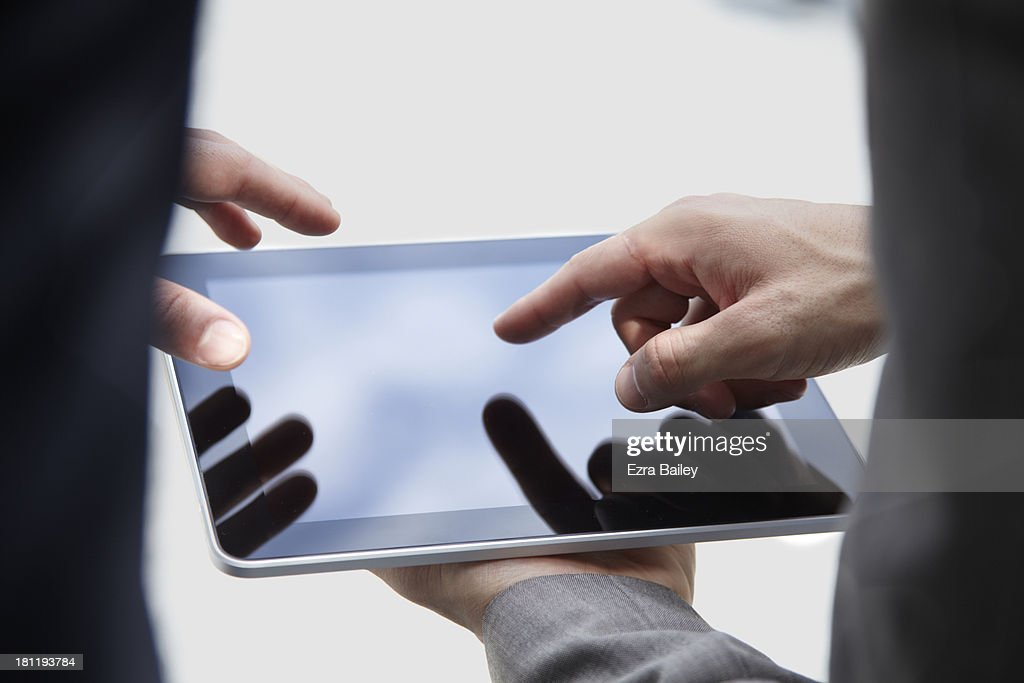 2 business men working on a tablet : Stock Photo