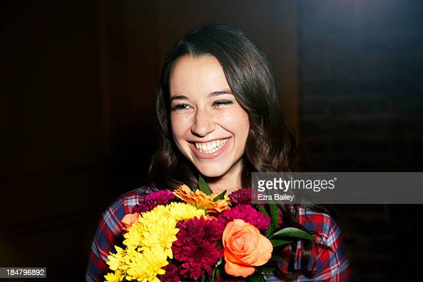 Woman smiling with a bunch of flowers.