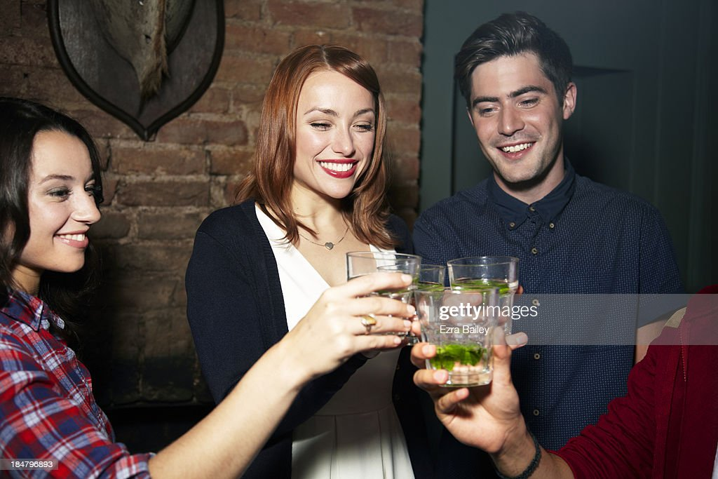 Friends drinking cocktails at a party.