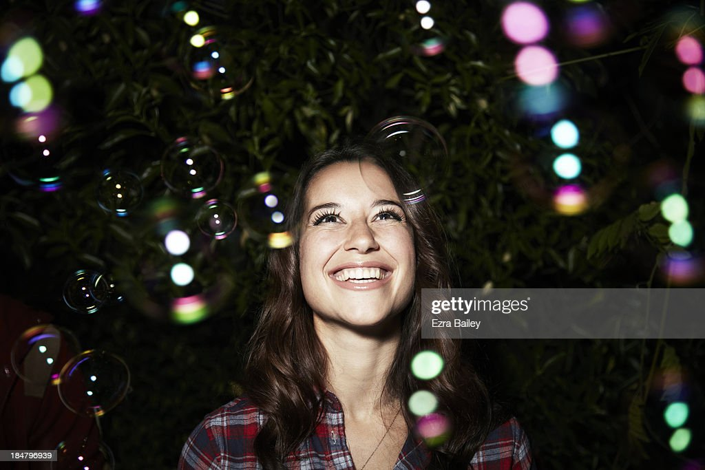 Woman surrounded by bubbles at a party.