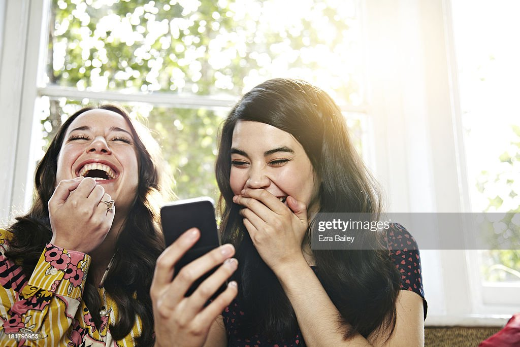 Friends laughing at a mobile phone : Stock Photo
