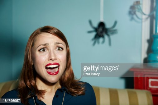 Shocked woman looking at spider.