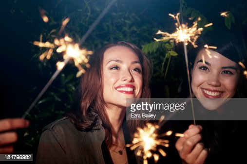 Friends with sparklers at a party.