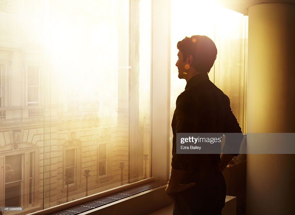 Businessman looking out over the city at sunrise. : Stock Photo