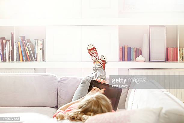 Woman using a tablet while relaxing on sofa