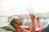 Young woman relaxing on sofa using a tablet.
