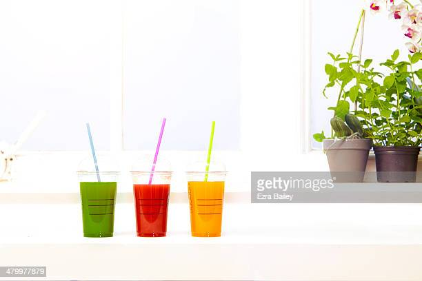 Three smoothies on a window sill with herbs.