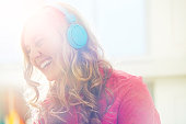 Woman wearing headphones and laughing.