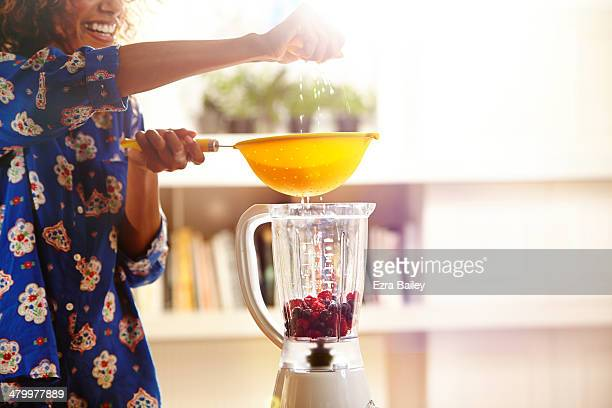Woman squeezing an orange while making a smoothie.