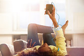 Woman relaxing at home listening to her phone.