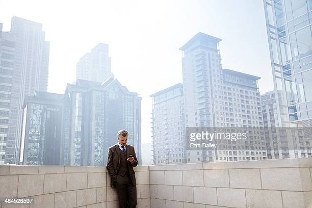Businessman checking his phone in the city.
