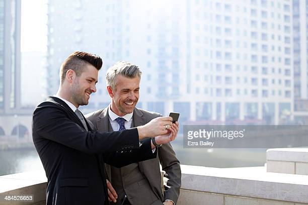Two businessmen laughing at a something on a phone
