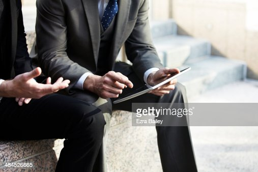 Two businessmen discussing plans on a tablet.