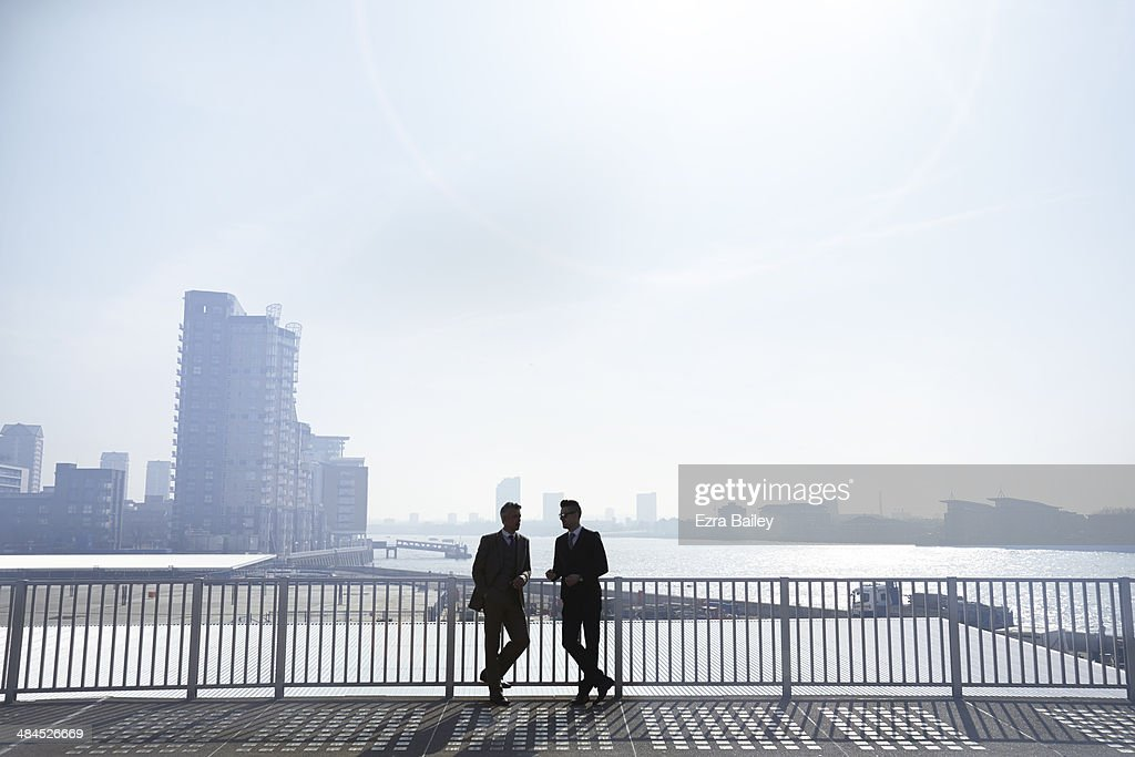 Two businessmen silhouetted against city skyline. : Stock Photo
