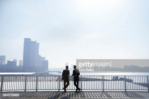 Two businessmen silhouetted against city skyline.