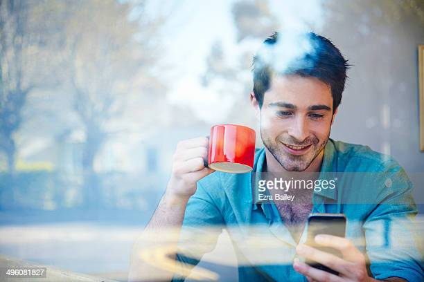 Man looking at his phone in a coffee shop window.
