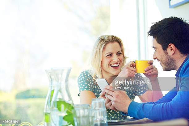 Friends laughing at a mobile phone.