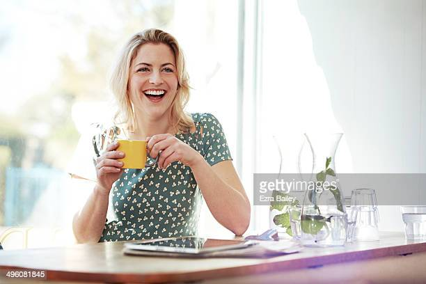 Woman laughing in a coffee shop
