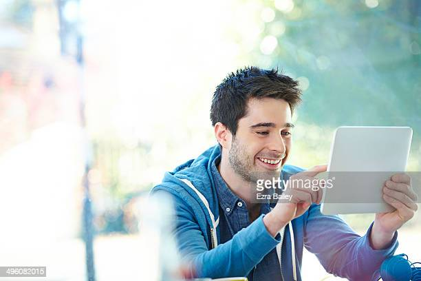 Young man using his tablet in a cafe.