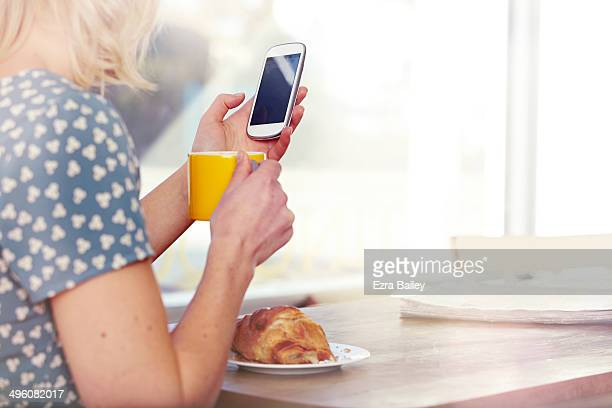 Woman looking at her phone in a coffee shop.