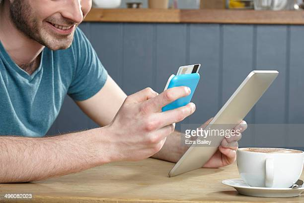 Man doing online banking in a coffee shop