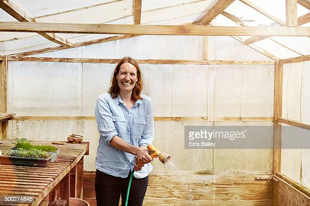 Woman laughing and watering plants in a greenhouse