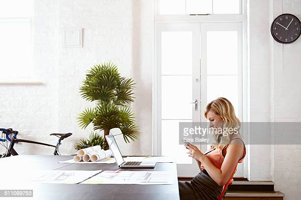 Young office worker on her phone at work.