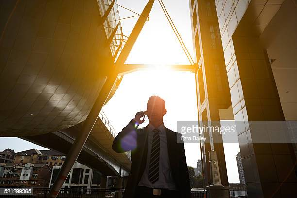 A businessman using a mobile phone at sunrise.