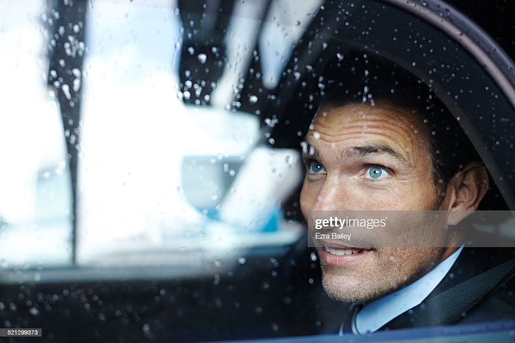 A businessman looks from a taxi window