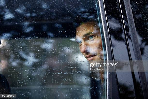 Businessman looks out of a taxi window.