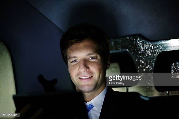Businessman uses a tablet in a taxi, at night.