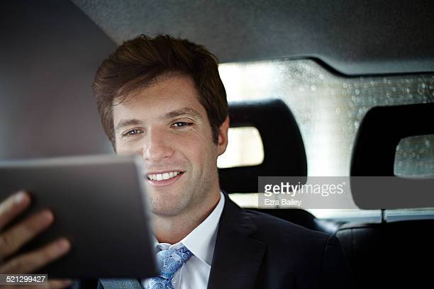 A businessman using a tablet device on a journey.