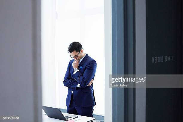 Businessman working on a laptop in clean office.