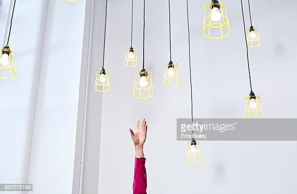 A hand reaching for conceptual idea lightbulbs