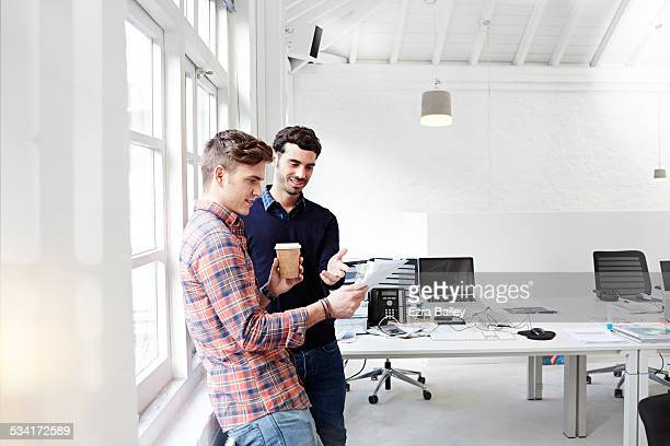 Two creative people chatting in modern office